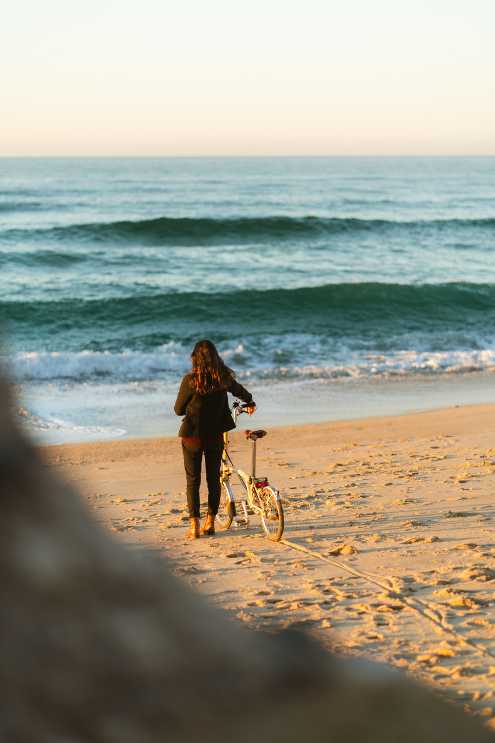 Girl walking in the sand with Brompton bike at sunset.