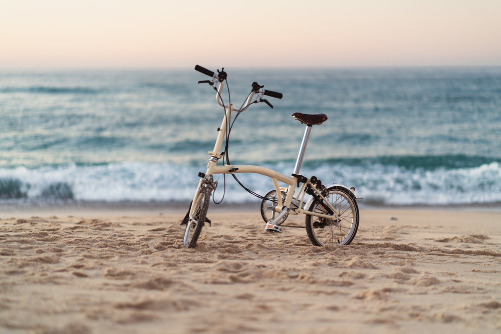 Brompton bike in the beach at sunset.
