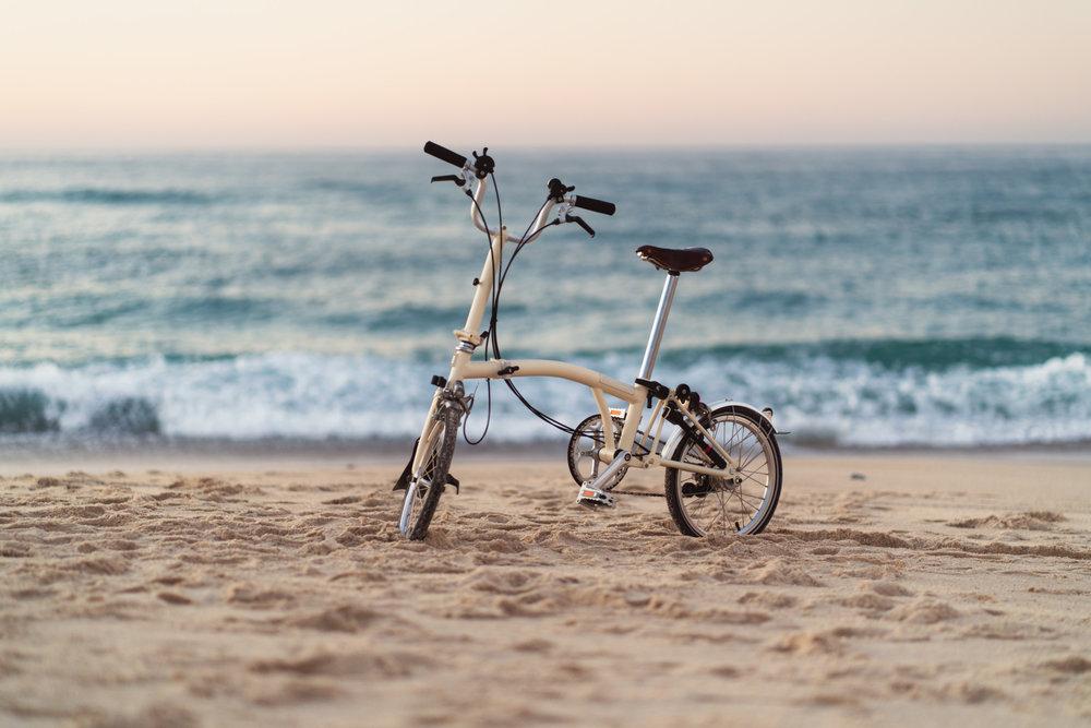 Brompton bike in the beach at sunset.