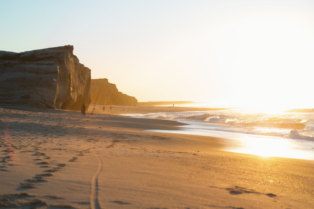 Golden hour beach with sand, fisherman, cliffs and waves.