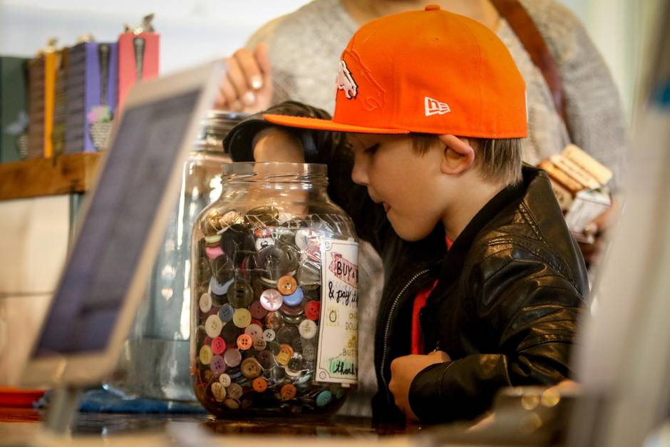 Ryder Fasulo, 7, reaches into the Button Bank at 541 Eatery and Exchange to buy a button for a dollar which will then turn into currency (valued at a dollar) that can be used by someone in need, towards a purchase of a coffee or a meal. Five buttons can be used per day per person.