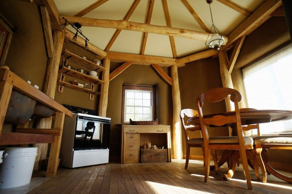 Beautiful smooth round wood surfaces on the  interior of a fire resistant cob home.