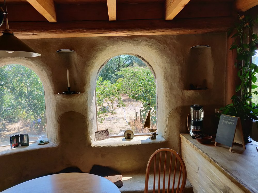 Small diameter round wood used as structural beams in this fire resistant, earthen encased home interior.