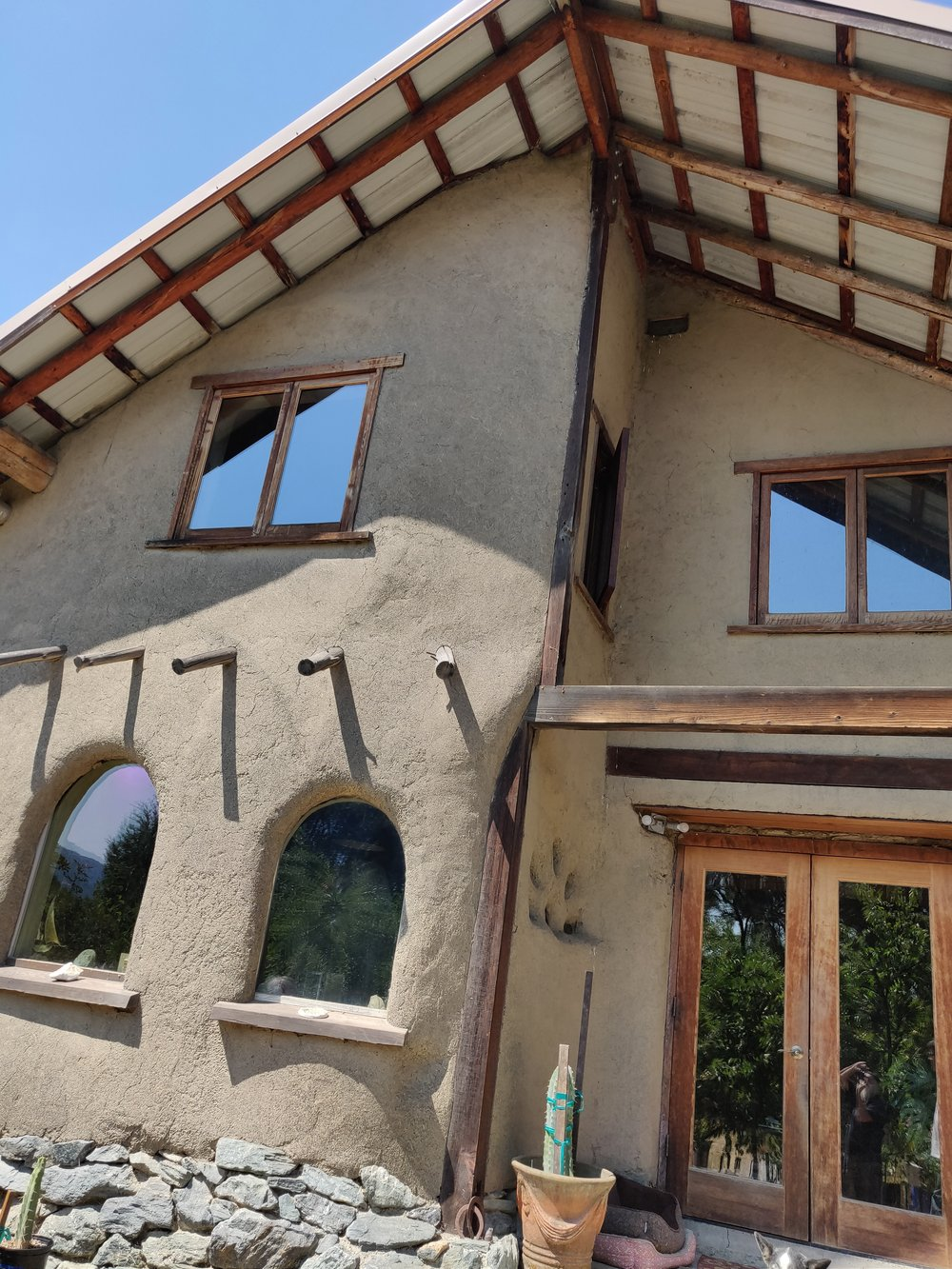 Round poles are used as timber framing for this fire resistant home using straw bale and thick earthen plaster enclosure. Outside Laytonville, CA. Designed and built by   Polecraft Solutions .