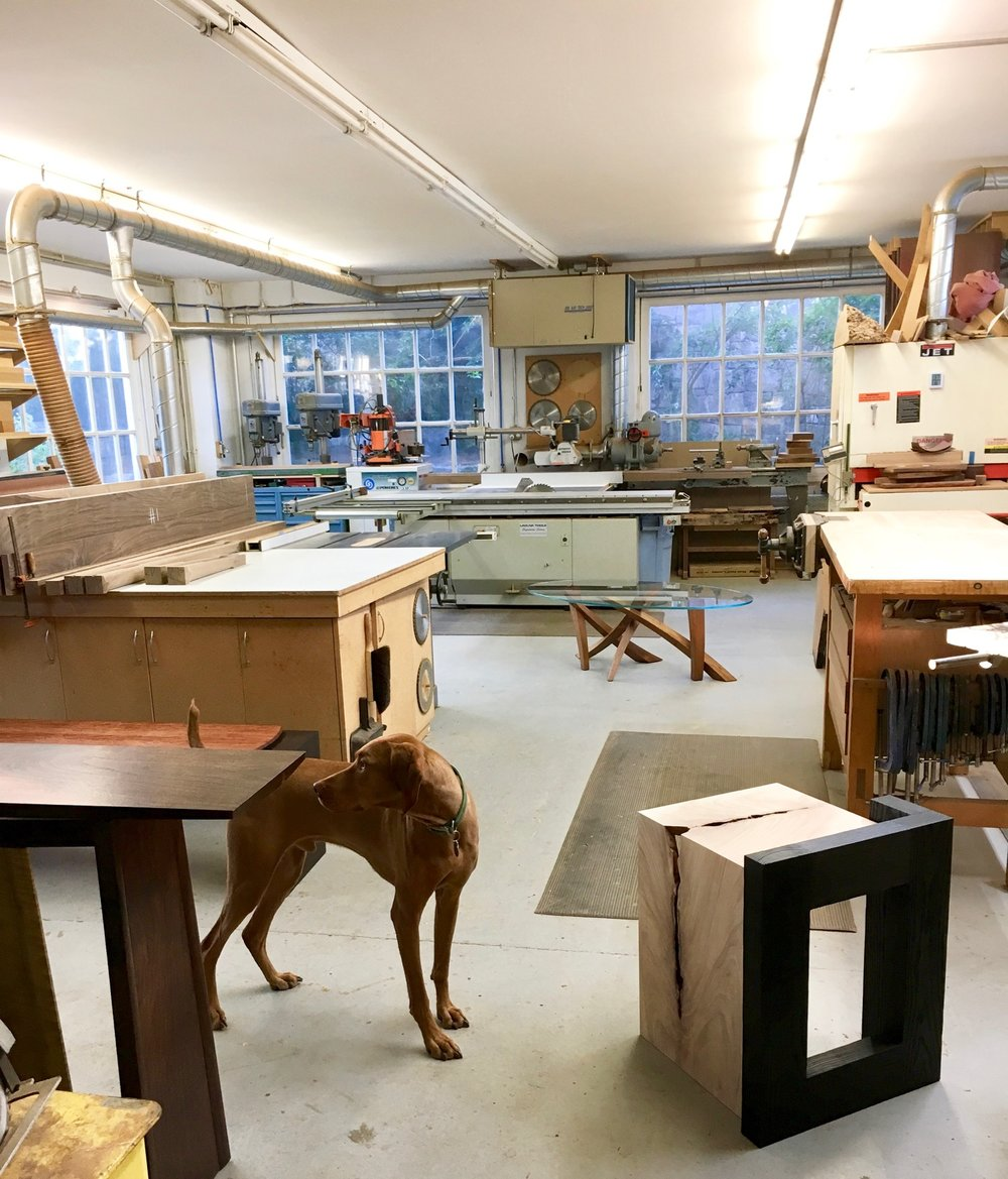 An array of furniture on display in the studio for a visiting client. In the background my bench space along with various machines both vintage and modern European. Our vizsla, Primo, has been the shop dog since 2014, preceeded by Radley and Simon both Vizslas.