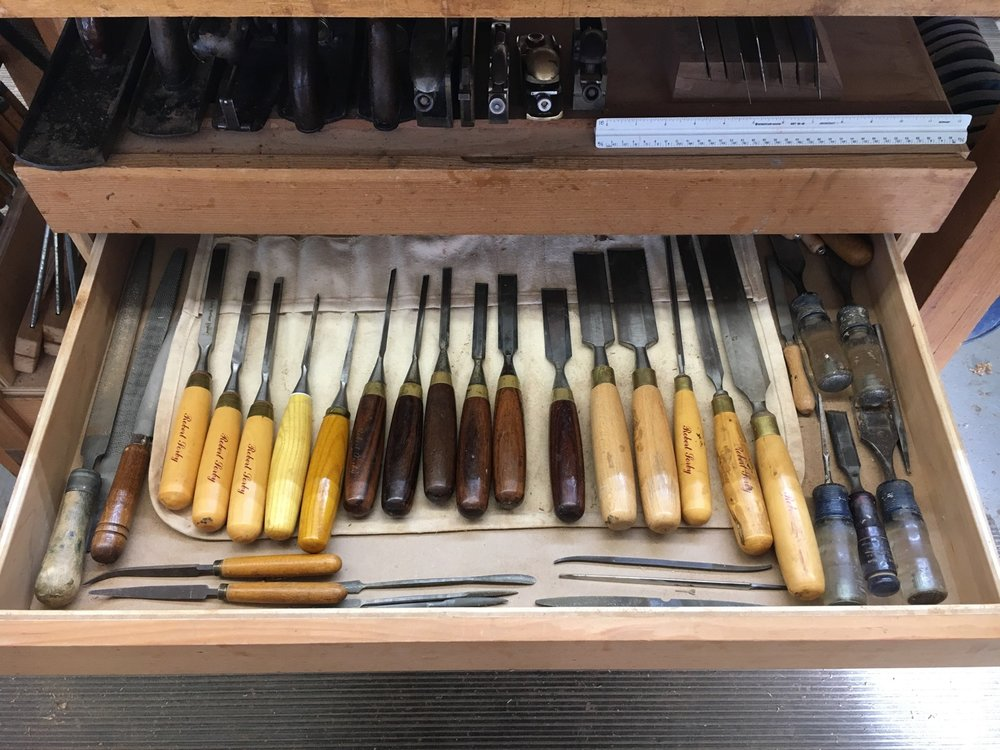 Various chisels with hand planes above