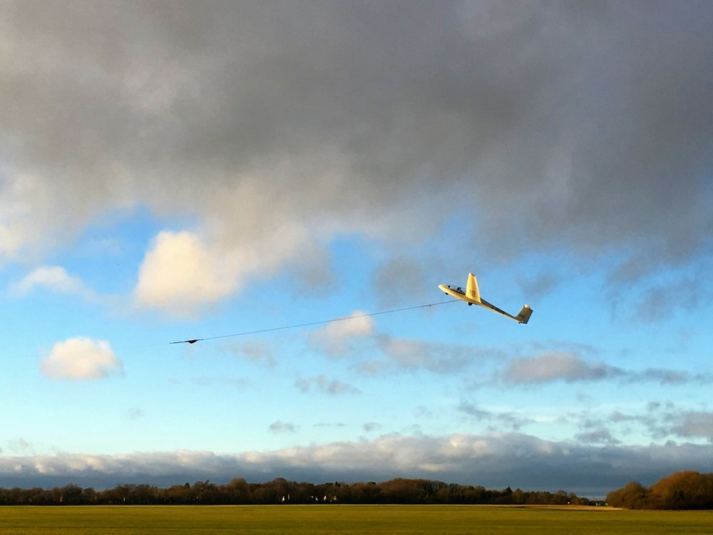 Winch Launch - A winch (about a mile off to the left in the picture) takes in a cable attached to the glider, pulling it forwards and providing airspeed. Once the glider is nearly over the winch the cable is released from the glider.