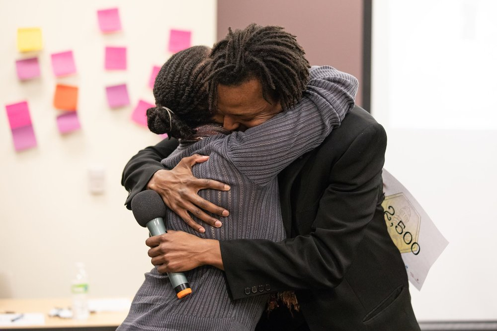 Photographer Shalicia Johnson from ArrowStar Photography gives a tearful hug to MABEE Founder, Eric S. Upchurch II after being awarded critical business funding.