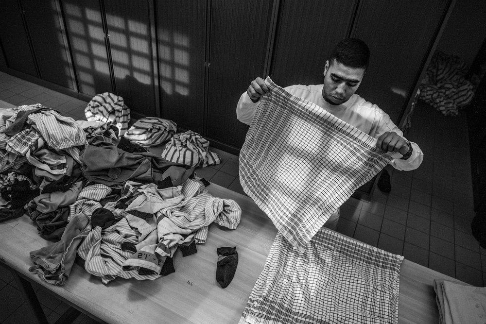 A inmate is folding the laundry inside the prison of Aundernaarde, 2015. © Sébastien Van Malleghem