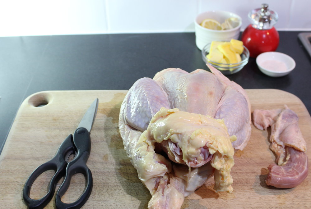 Step 1: Getting Ready - Preheat the oven to 160°C and gather your supplies: 1/2 lemon; a bulb of garlic, skin on, sliced open across the bulb; 70g grass fed butter, chopped in to sticks; Himalayan pink salt or sea salt; and black pepper.If you bought your chicken frozen, make sure that it is completely thawed. I defrost mine in the fridge for a good three days before I plan to cook it. Give the chicken a rinse and pat it dry with paper towel, inside and out. Cut off the neck with a pair of kitchen scissors and set aside in the freezer for making stock.