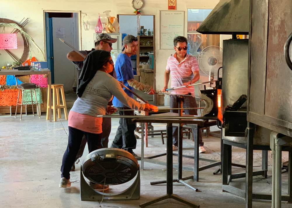 A group of artisans blowing glass.