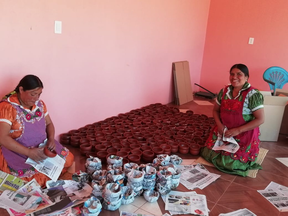 Two artisans wrapping red clay pottery in newspaper.