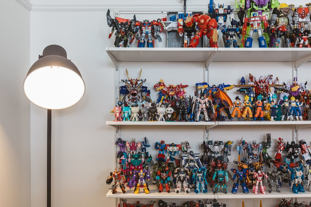 The couple found the perfect way to organize and display Kyle's collection of transformers using simple white shelves.