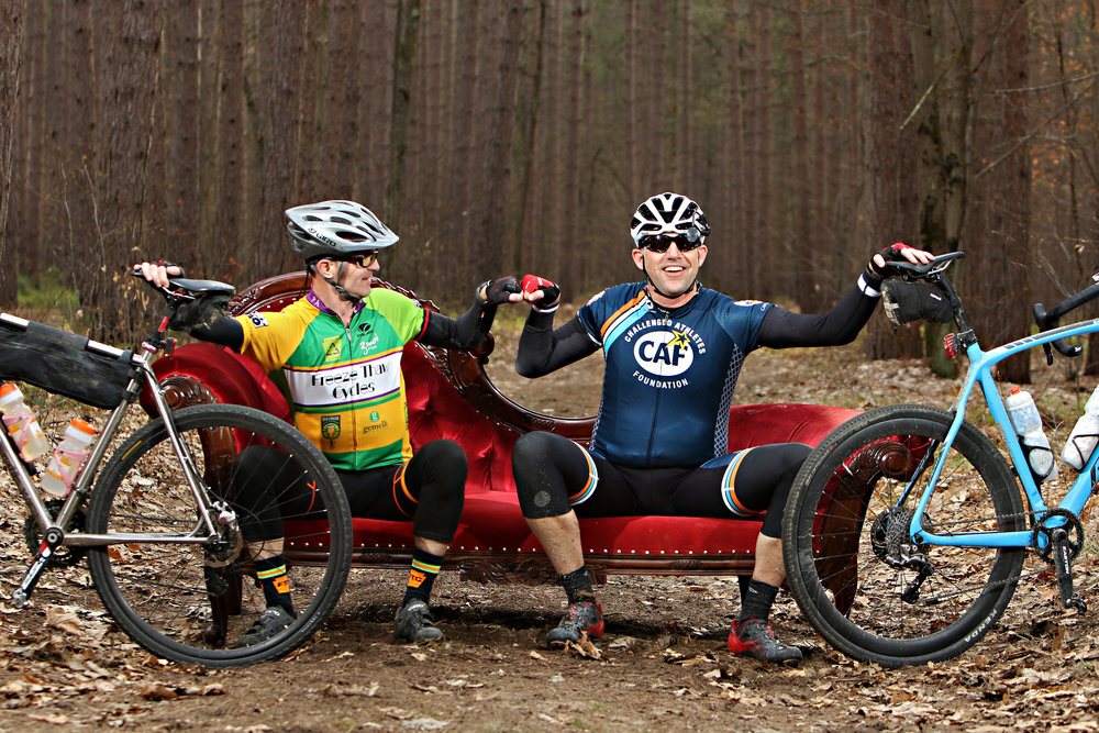 "The Salsa bike company drove around the country in 2018 with a velvet red sofa. Their ""Chase the Chaise"" campaign enticed riders to find and get photographed on the couch which is positioned late in the race course. Here it is located deep in the Michigan woods at Mile 170 of the Coast to Coast gravel race. This is the kind of fun spirit that embodies the gravel racing scene. Even the top pros stopped briefly to get their picture taken."