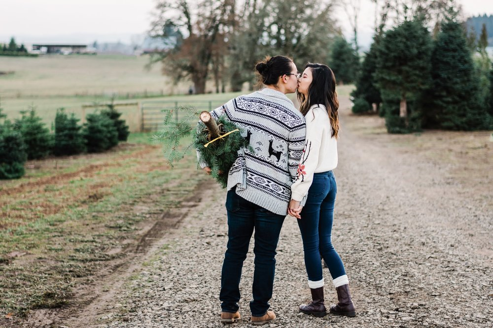 engaged couple kissing with Christmas in Portland Oregon