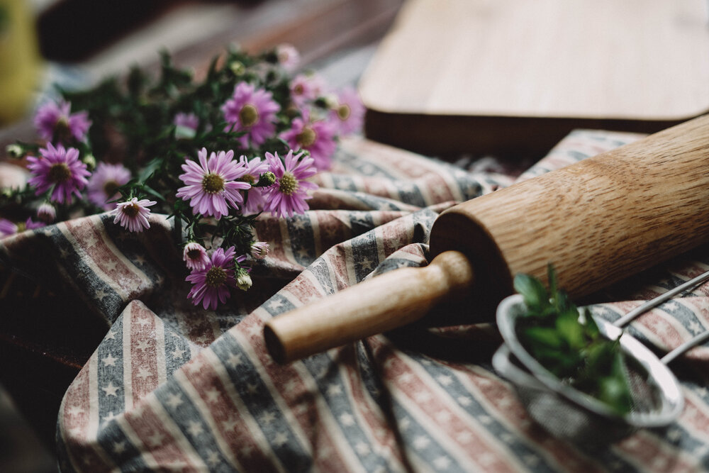 A vintage wooden rolling pin is pictured laying on a stripped linen cloth with fresh flowers to the left and fresh herbs and a strainer to the right. There is a wooden cutting board in the background.