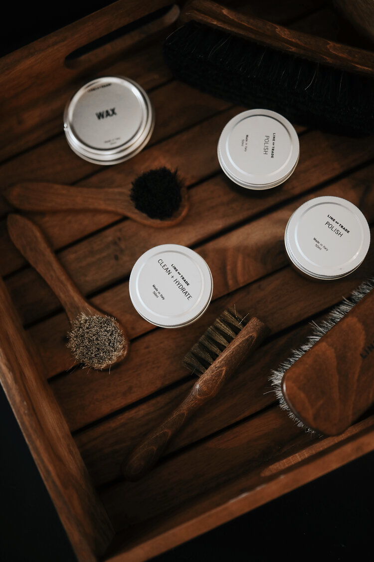 An overhead picture of brushes, oils and waxes in a wooden crate.