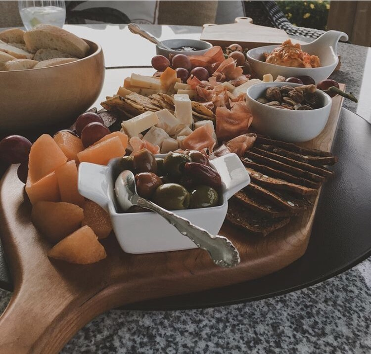 A wooden charcuterie board is pilled high with cheese, meats, veggies and dips.