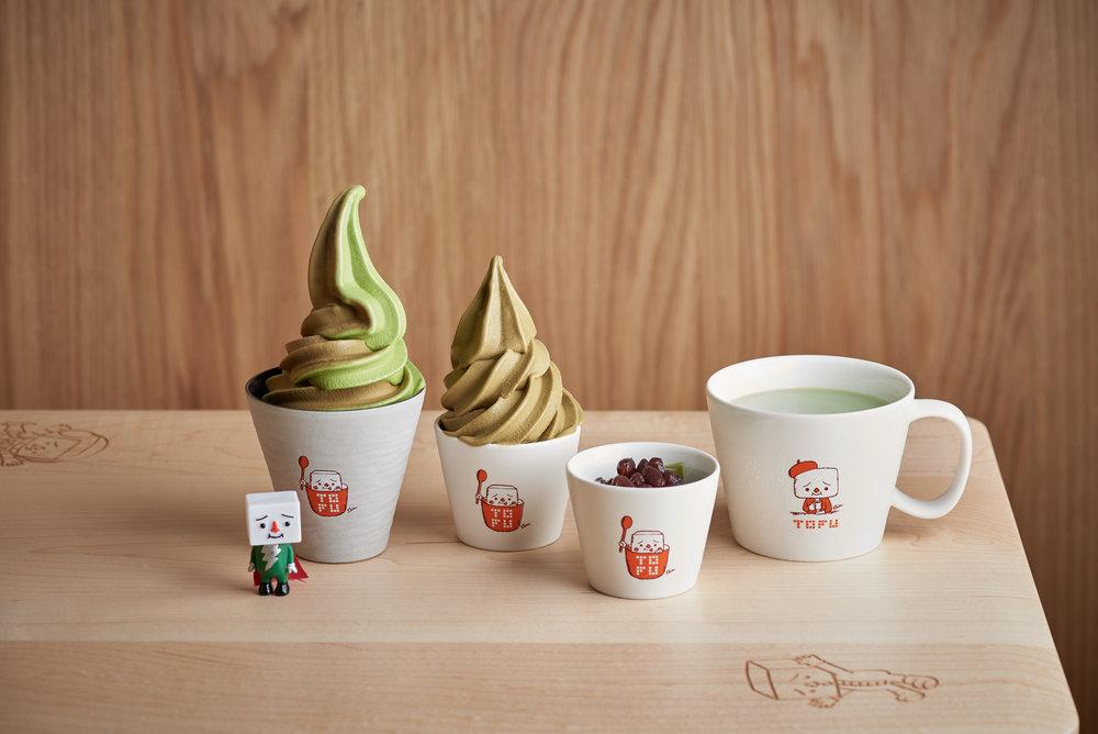 一般對「公仔商品」的認識只著重在圖像利用與大量生產,未能顧及商品品質與實質體驗。這次「豆腐找茶」與「玩味創研」合作,精選八個台灣在地品牌,從燈具、傢具、餐盤到食器,與日本設計師合作重新創造,將豆腐人的形象與圖案進一步結合其中,創造店內獨特的用餐體驗,並推出這些傢具及餐具的獨特限量聯名商品。  我們依照店內的氛圍、菜單的規劃,訪查品牌商品完整性、調性,在一個月內溝通了八個品牌與豆腐人進行跨界聯名合作 – 從燈具、實木桌、凳子、高腳凳、木托盤、瓷盤、陶杯、玻璃杯、木湯匙、高級茶選、原生可可豆、巧克力等。八個品牌的設計師,以自有的線上產品,進行與豆腐人的圖像聯名。乍看之下,豆腐人粉絲們孰悉的符號依舊,但是,器物變精緻了、有文化脈絡了,也承載了設計師在構思、選材、製作及包裝的故事。這些,成為了在地生活產品設計介接插畫角色粉絲經濟市場的突破點。從這裡,開啟了兩塊鄰近卻又遙遠的平行時空對話的可能。