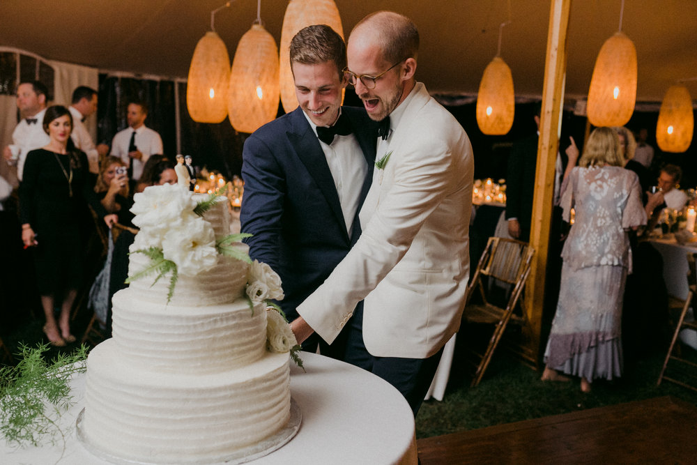 Same Sex Wedding in Provincetown, MA. Destination wedding planned by Nicole Simeral. Coastal Chic Wedding, Travel Wedding, Sperry Sailcloth Tent Wedding, bamboo folding chairs, Belfast linen, whites and greens , straw lantern, symmetry , cake cutting