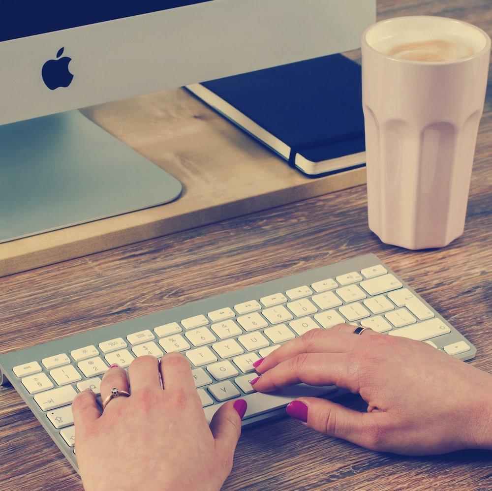 Hands of Female Custom Software Developer on Apple Keyboard