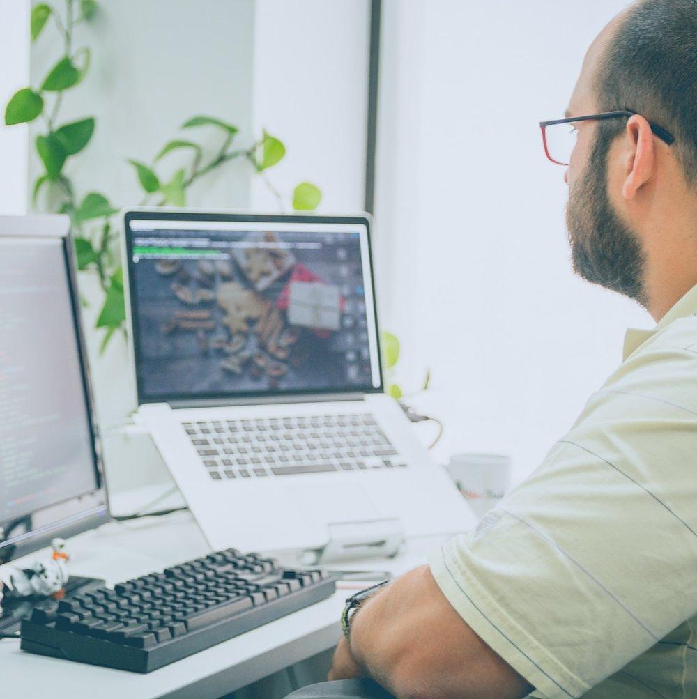 Male Custom Software Developer Working on Laptop and Desktop