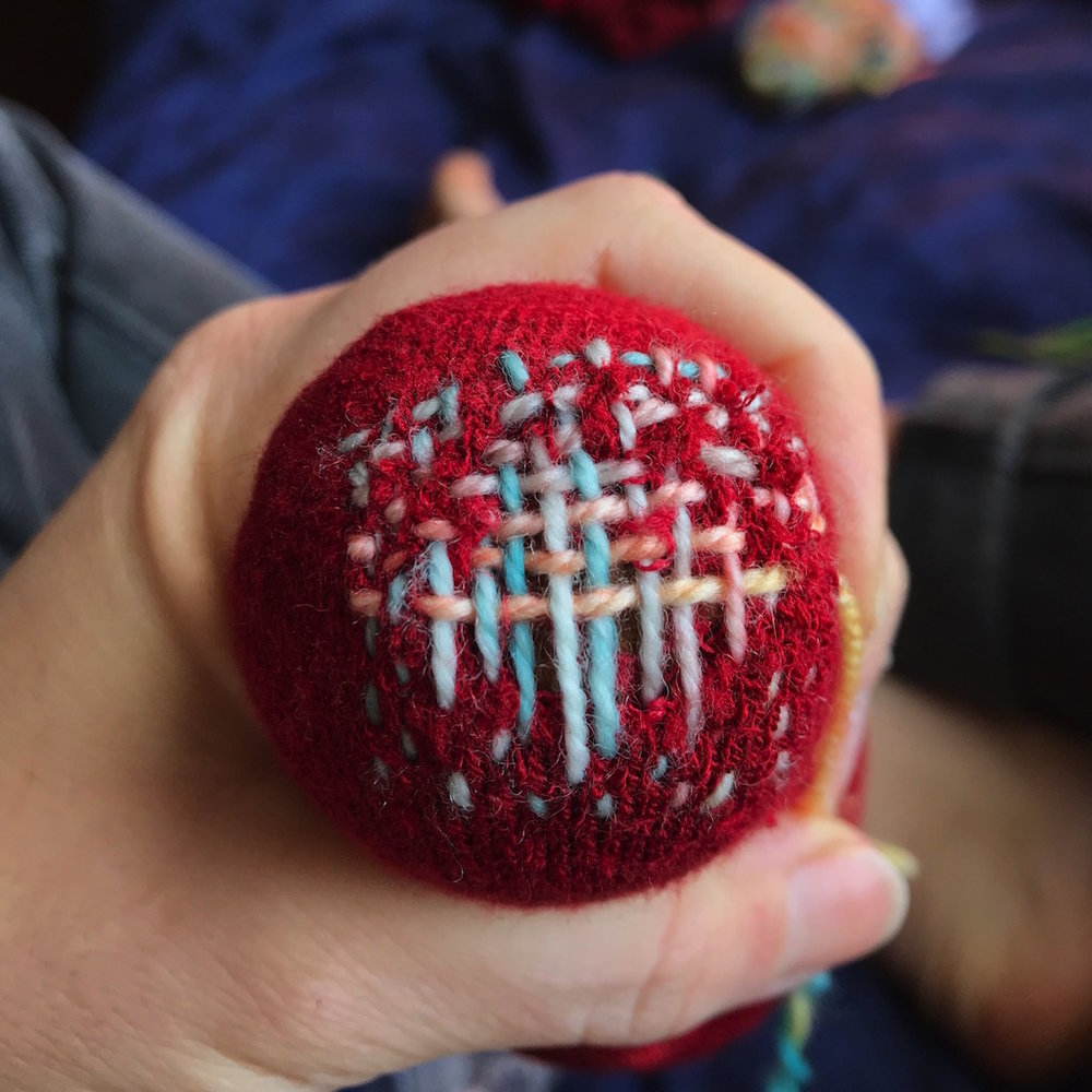 Sock darning, using a vintage darning egg. This process can be done with decorative or matching yarn.