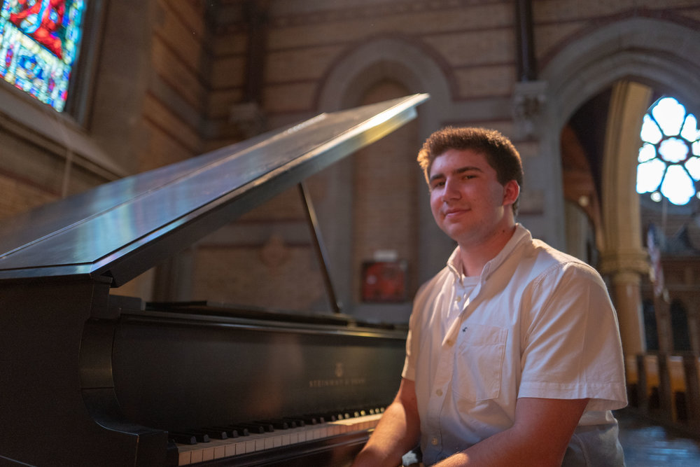 Justin in a beautiful church while playing piano.