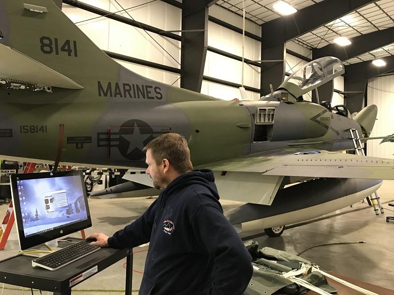 mechanic uses computer for aircraft maintenance