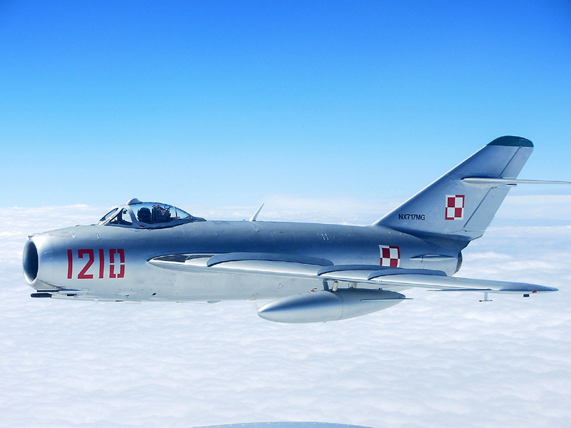 Mikoyan-Gurevich MiG-17 flying in blue sky with clouds