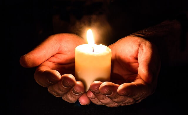 Hands holding a lit candle.