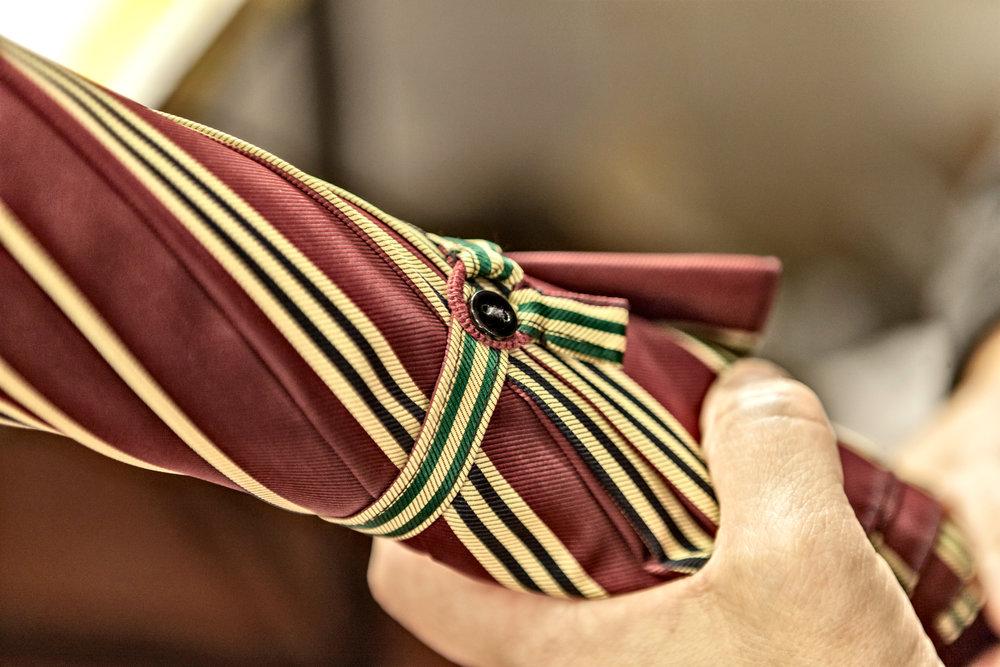 Detail of an hand-sewn umbrella's closing band.  Photo credit: LucaPradella