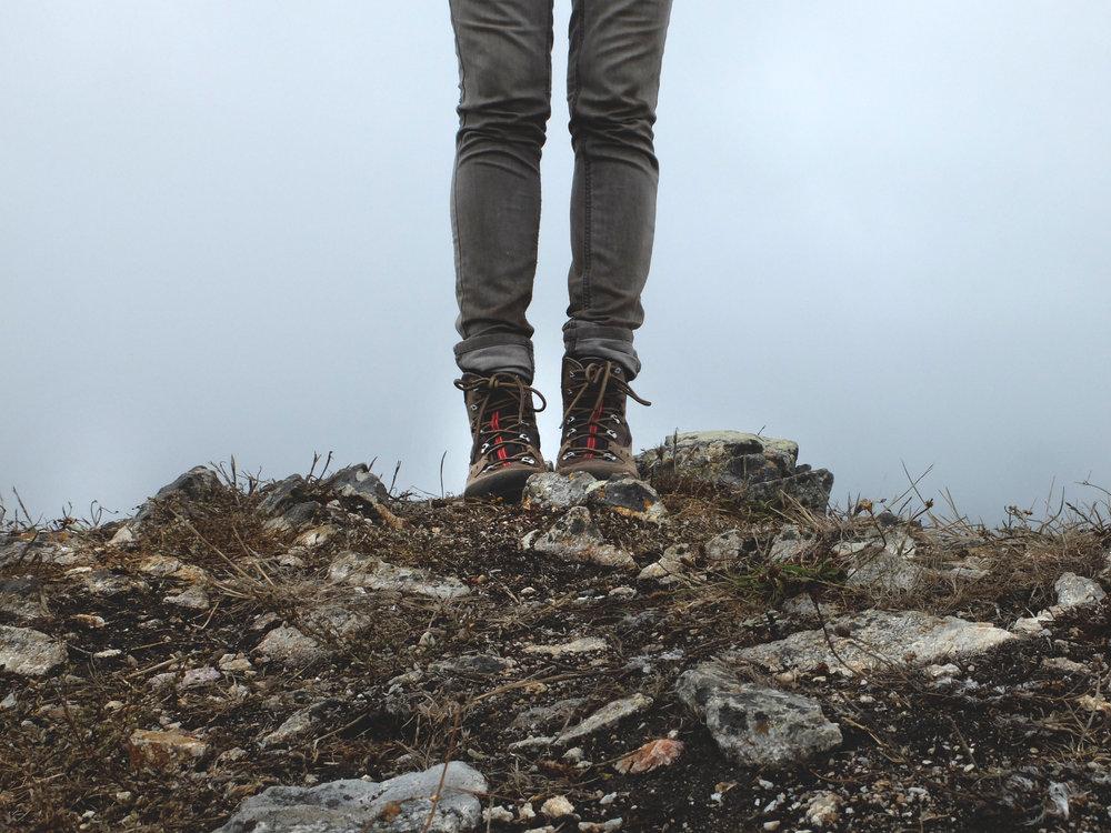 walker in hiking boots on top of rocks
