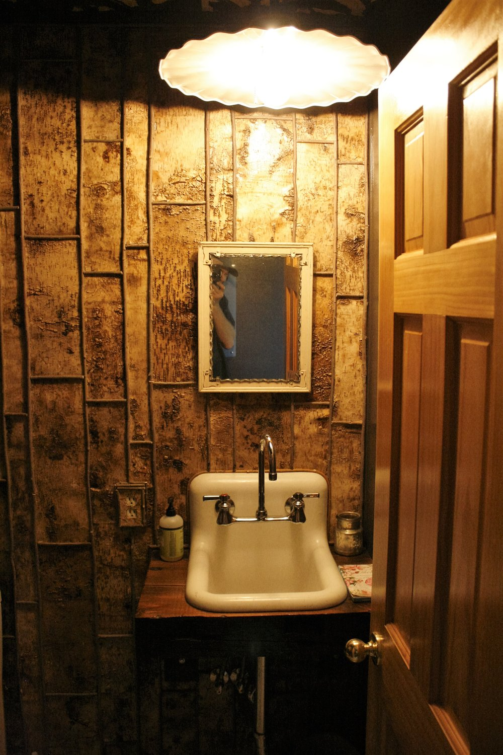 Custom made vanity, birch strip wall covering, on property willow branch trim, and vintage light install