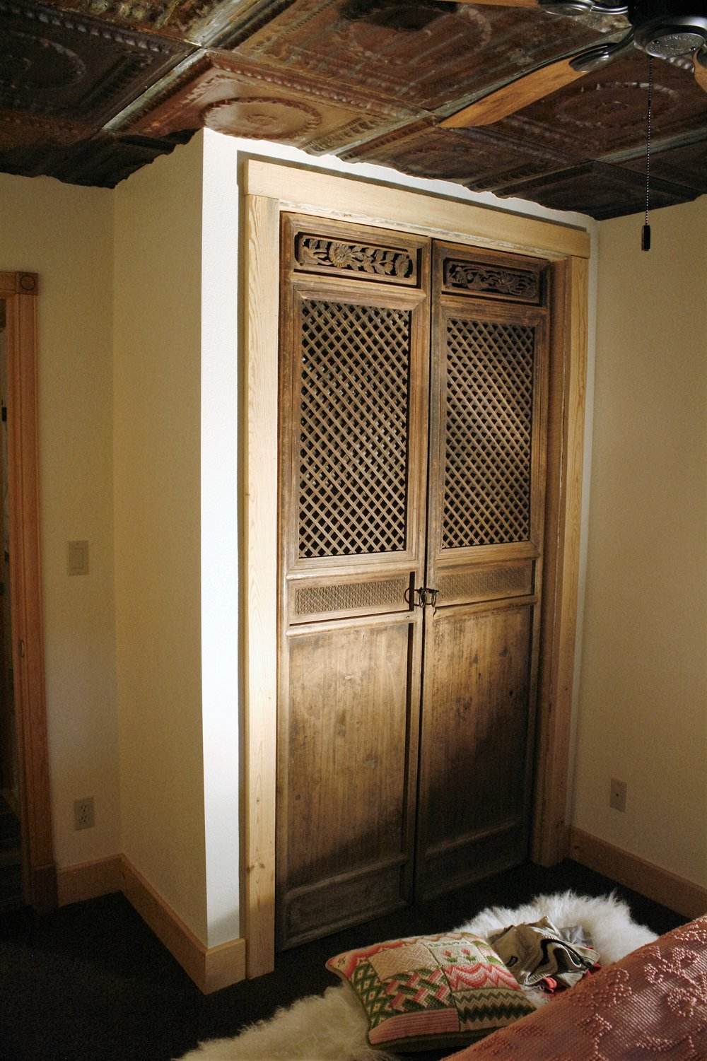 After image of closet with; drywall, texture and paint, vintage pivot swing doors and tin ceiling