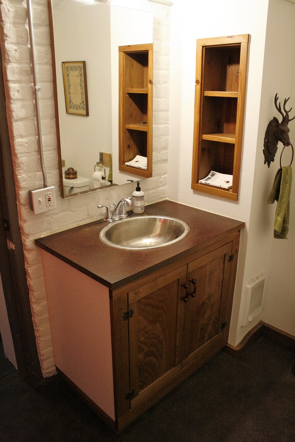 Custom cabinetry and rusted metal vanity top, custom shelf, and sanded, stained, sealed floor
