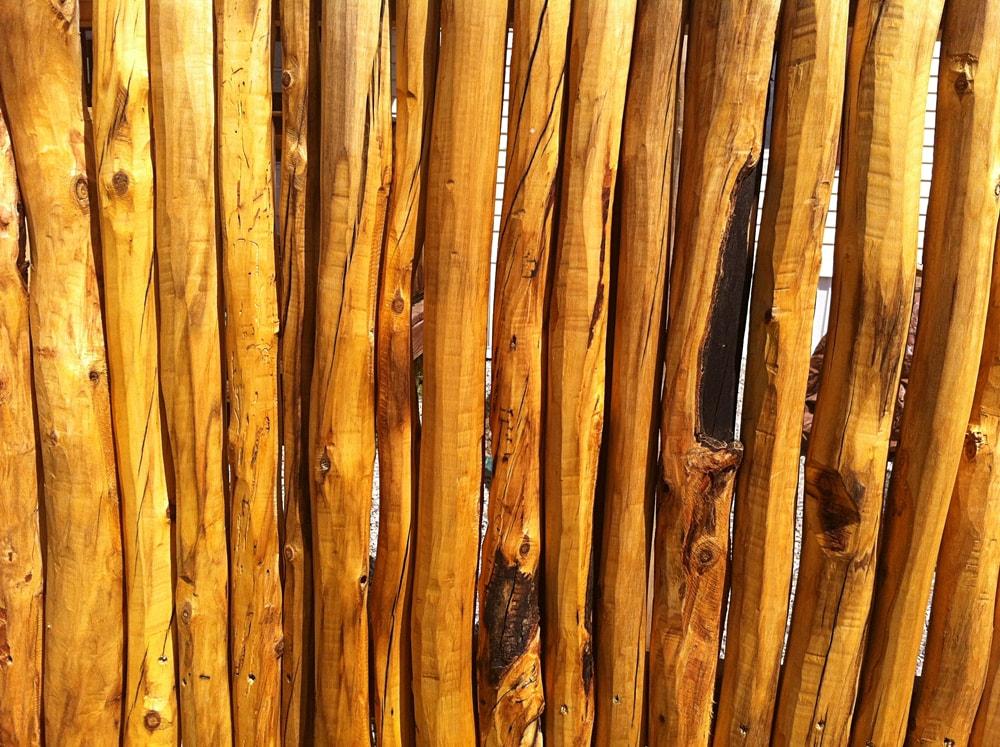 Close up of hand peeled aspen log fence
