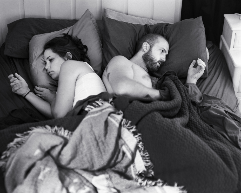 Self portrait of the artist Eric Pickersgill and his wife Angie as they lay back to back while using thier non existant phones. The black and white portrait shows the young couple ignoring each other in bed.
