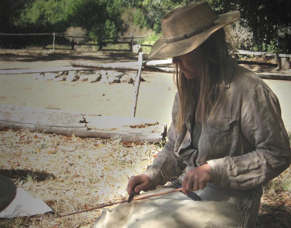Tamara scraping a dogbane stick before extracting fiber