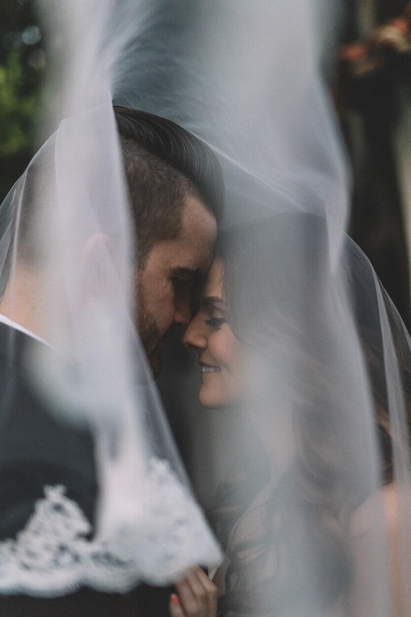 couple entrelacé sous le voile de la mariée profitant du moment