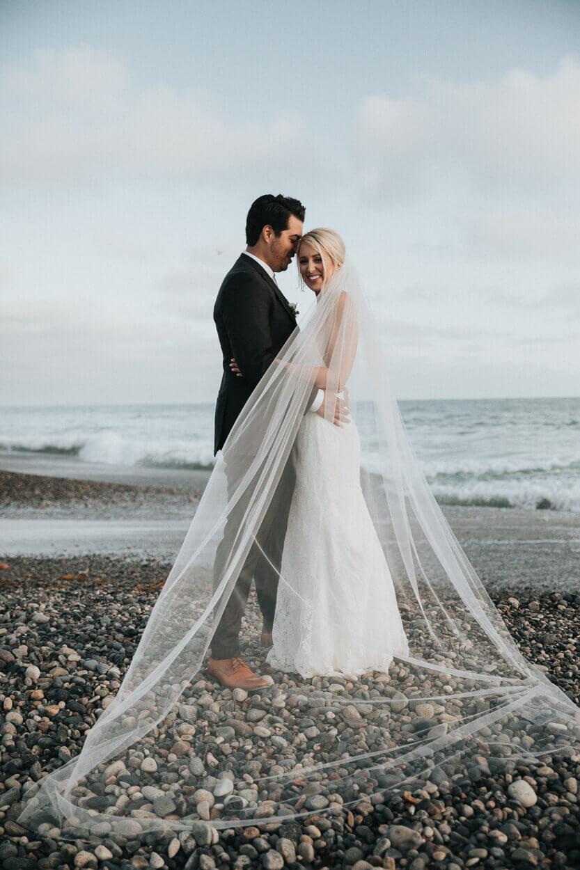 couple l'un contre l'autre sur la plage avec le voile de la mariée
