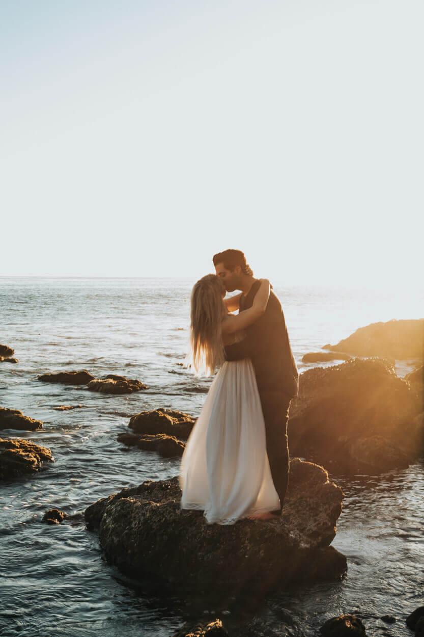mariée s'embrassant sur un rocher au coucher de soleil