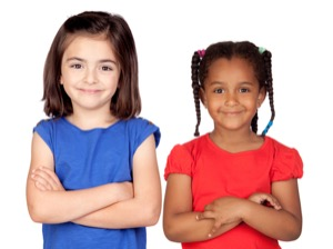 two-adopted-girls-with-crossed-arms-in-front-of-a-white-background.jpg
