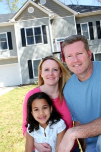 a-happy-couple-with-an-adopted-daughter-outside-their-home.jpg