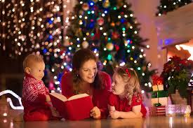 mother-with-christmas-tree-behind-reading-book-to-her-two-chidlren.jpg