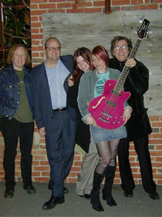 Shalini receiving a Waterstone 12-string bass. Left to right: Mitch Easter, Bob Singer of Waterstone, Alison Petersson, Shalini, Tom Petersson.