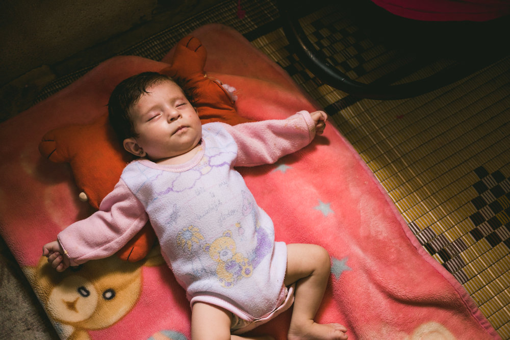 "A newborn baby sleeping in an ""unofficial"" refugee camp in the Bekaa Valley."