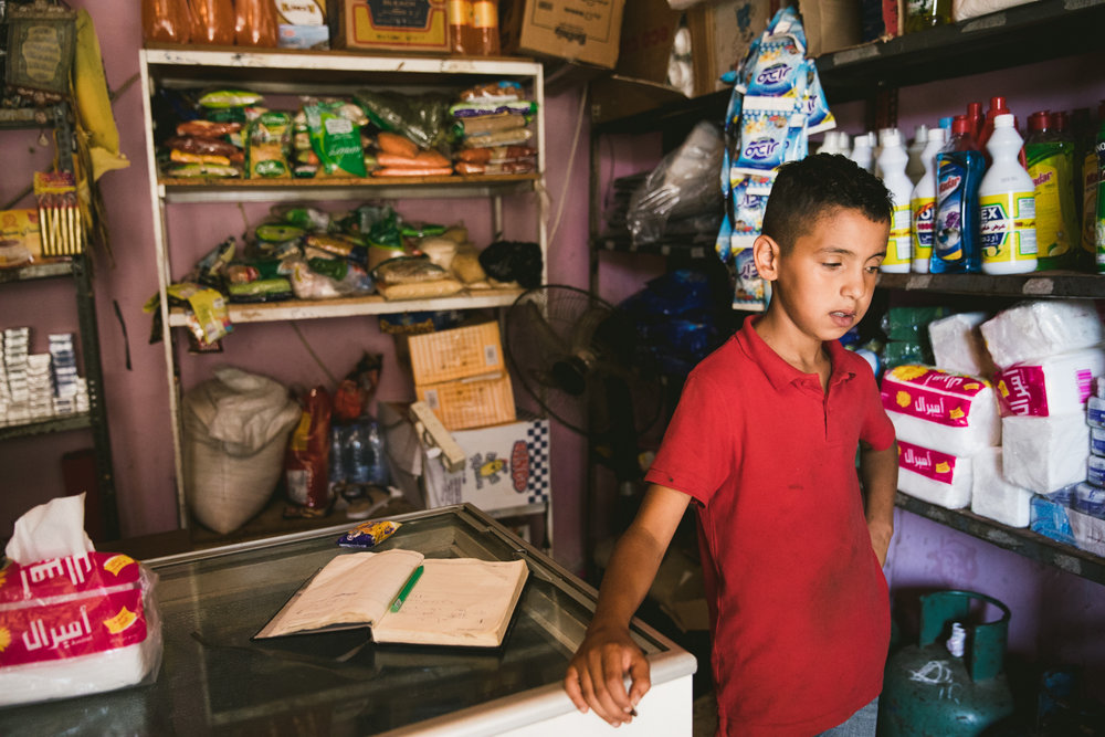 A young boy standing in his family's small shop inside the Shatila camp. As most of refugees lack a regular source of income many products are purchased on loan, and ledgers keep track of the community debts.