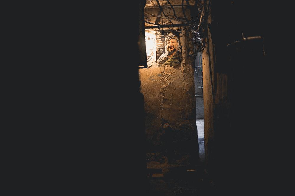 A lone light bulb illuminates a photo of Yassar Arafat.