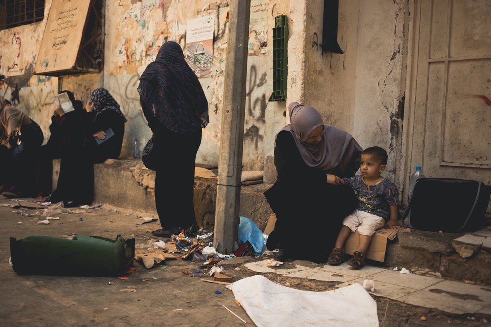 Mothers and children wait near the office of the PLO inside Shatila.